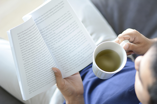 A man reading book with hot tea cup in another hand